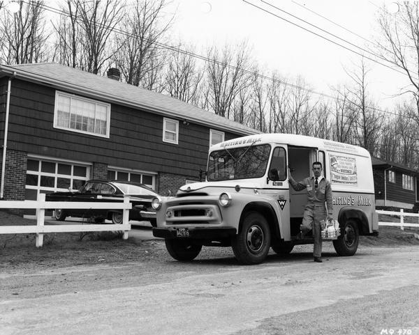Milkman making a delivery from an International A-140 Metro milk truck. The truck was owned by Whiting's Milk.