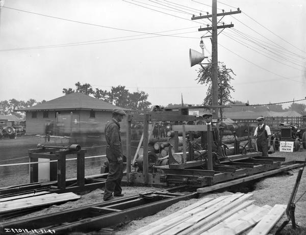 Three workers using a portable sawmill to cut wood, possibly at a fairgrounds. A McCormick-Deering industrial tractor sits in the background.
