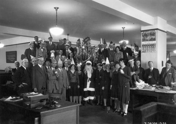 "International Harvester employees standing around a Christmas tree and Santa Claus during an office party. Many of the workers are wearing party hats and some are holding American flags. The Santa appears to be wearing a mask. The party was described in ""Harvester World"" magazine as ""the second annual Christmas party of the order and distribution department, Chicago office."""