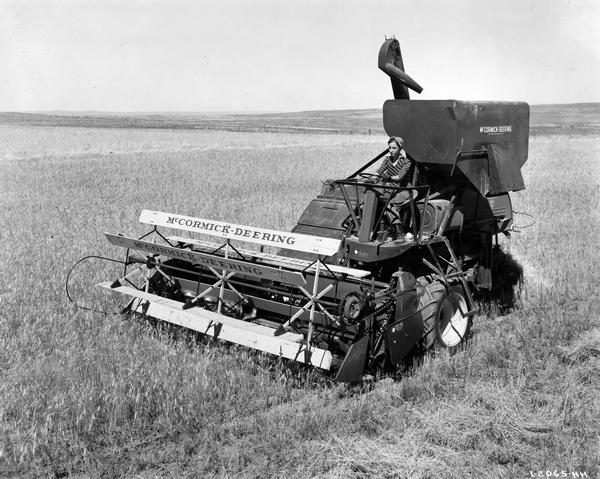 Slightly elevated view of fifteen-year-old Peggy Wold operating a McCormick-Deering 123-SP (self-propelled) harvester-thresher (combine) on the farm of Carl Gullard.