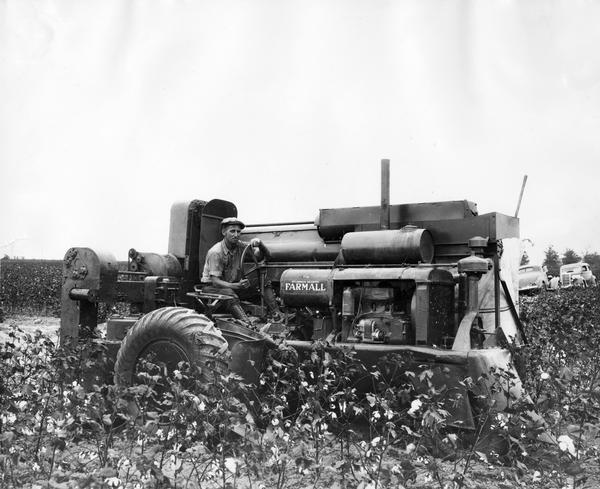 "Man operating an experimental International Harvester cotton picker in a cotton field on the Hopson Plantation near Clarksdale, Mississippi.  Two automobiles are parked in the background. Original caption reads: ""View showing picker unit side of International Harvester cotton picker. Picker unit is raised or lowered by turning screw near right arm of operator."""