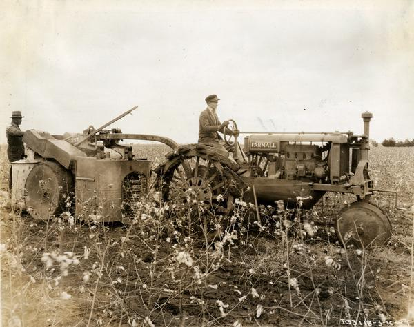 Right side profile view of a man pulling an experimental pull-type cotton picker through a cotton field with a Farmall Regular tractor. a Another man is standing at the back of the cotton picker.