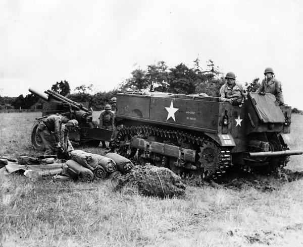 "Soldiers pulling 155mm howitzer with an M-5 tractor at Camp Adair, Oregon.  The original caption reads:  ""This is the new M-5 tractor which replaces 2 and one-half ton trucks as the standard prime-mover for the big new 155 mm howitzers.  The tractor jockey is rated a member of the gun-crew of 10 men crew members (background) are picking up trails of gun preparatory to hooking on."""