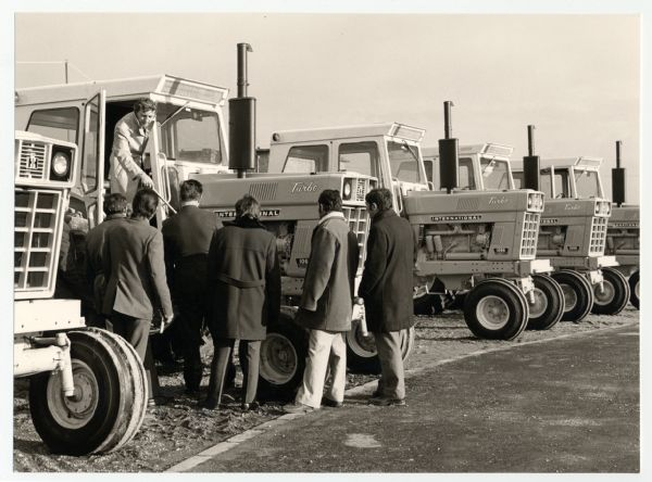 Men looking at International 1066 turbo tractors at the Babolna State Farm in Hungary.