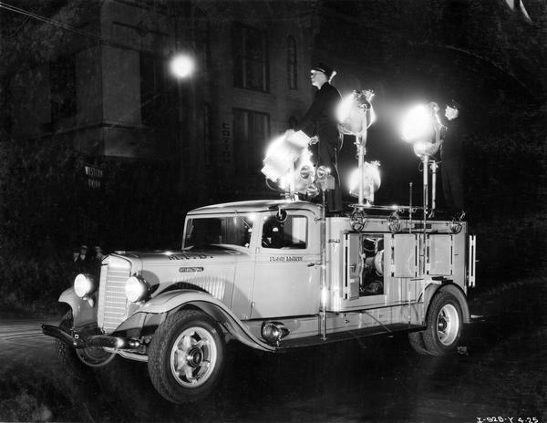 International Model C-40 fire truck with floodlights. The truck was owned by the Memphis, Tennessee fire department.  A man stands on top of the truck and guides a flood light to a nearby building.