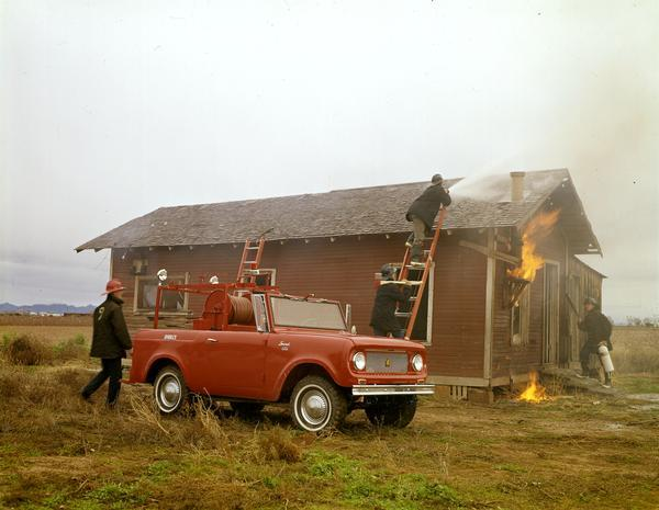 Color photograph of a fire crew battling small house fire during a training exercise. The men are using an International Scout fire truck.