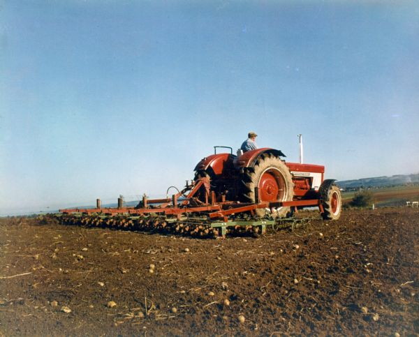 Color photograph of a man operating an International tractor with in a field in Germany.