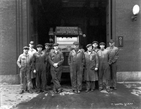 International Harvester workmen wearing coveralls are posing in front of an International Harvester motor truck outside a service garage at a dealership.