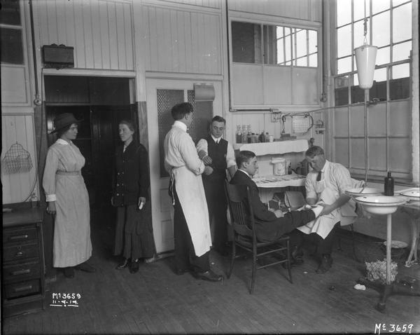 "Medical staff attending to male and female factory workers at International Harvester's McCormick Works. The factory was owned by the McCormick Harvesting Machine Company until 1902 when it became International Harvester's McCormick Works. It was located at Blue Island and Western Avenues in the Chicago subdivision called ""Canalport."""