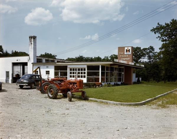 "Color photograph of tractors and a car parked in front of the Fisher Company store, an IH dealership. This ""prototype"" dealership building was built as part of International Harvester's ""Dealer Base of Operations Program."" By February of 1948, 386 dealerships had been built on the prototype plan. Another 617 dealerships were under construction or had been built on a modified prototype plan. Eventually over 1800 such dealerships were built worldwide."