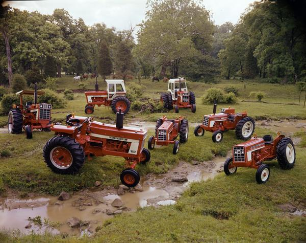 Color advertising photograph of the International tractor family arranged for display around a rural creek. Tractors include (from front, clockwise): Farmall 766, Farmall 1466 Turbo, Farmall 966, Farmall 1066 Turbo(?), 574, 354, and 454.