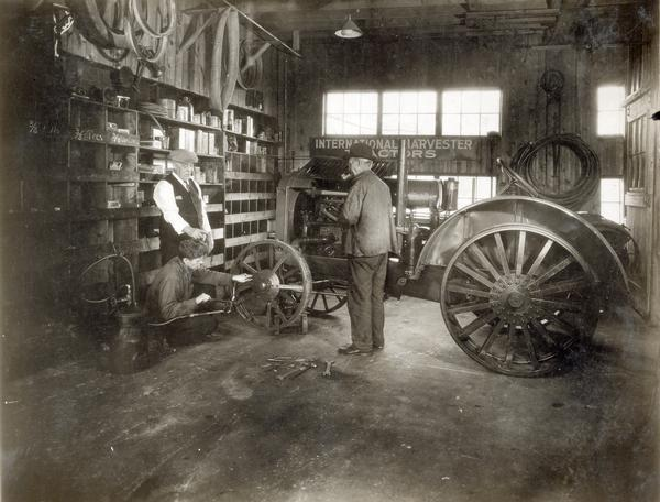 Mechanic works on the front wheel of an International tractor in  service shop of the International Harvester dealership of Dan Pullin and Son.