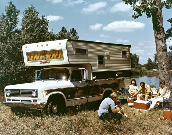 Color advertising photograph of a family camping near a lake with an International 1310 pickup truck and a Monitor camper.