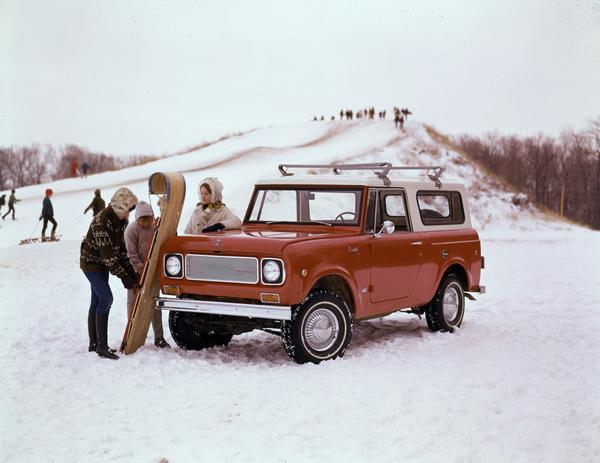 Color advertising photograph of a woman and two children with a toboggan and an International Scout 4x4 pickup truck. A snow-covered sledding hill is in the background.