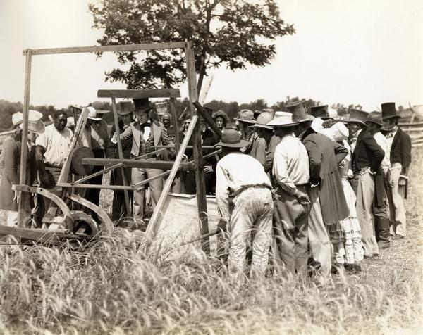 "Still from the feature length motion picuture ""Romance of the Reaper"" showing a recreation of the demonstration of Cyrus McCormick's reaper of 1831. The film was produced by the International Harvester Company to celebrate the 100 year anniversary of the invention of the reaper, also known as the ""reaper centennial."""