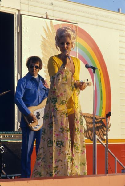 "Bonnie Nelson (a.k.a. ""Transtar Rose"") singing country music with a band on her truck stop tour. The tour ran in the summer of 1975 from Omaha to Des Moines. The tour promoted International Transtar trucks."