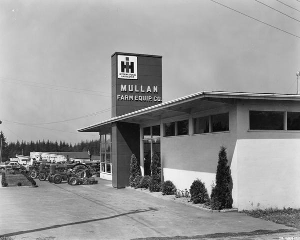 """Prototype"" dealership building of the Mullan Farm Equipment Company. An OS-4, Farmall C and Farmall AV tractor are parked outside the building. This ""prototype"" dealership building was built as part of International Harvester's ""Dealer Base of Operations Program."" By February of 1948, 386 dealerships had been built on the prototype plan. Another 617 dealerships were under construction or had been built on a modified prototype plan. Eventually over 1800 such dealerships were built worldwide."