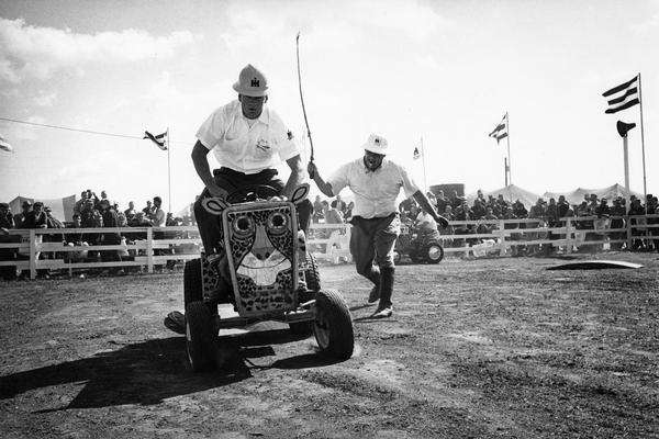 "Men riding Cub Cadet lawn tractors in International Harvester's ""wild-animal"" act at the Farm Progress Show in Farmer City, Iowa.  Three International Harvester salesmen piloted the jungle cat Cub Cadet tractors and George Mann, a professional actor, played the part of ""Fisbee"" the ""hapless animal trainer""."