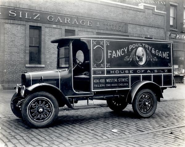 "S-speed truck owned by House of A. Silz and parked on the street in front of Silz Garage. The side panel of the truck includes an advertisement for ""Fancy Poultry and Game."""
