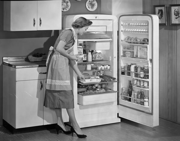 Woman demonstrates the features of a well-stocked International Harvester refrigerator.