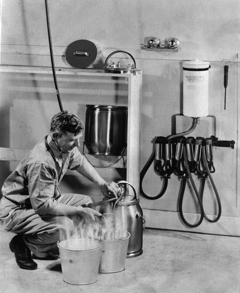 A man demonstrates how to use a McCormick-Deering milking machine.