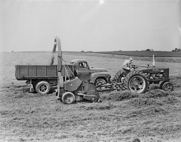 Men operating a Farmall Super M-TA tractor, a forage harvester and an International R-150 truck.