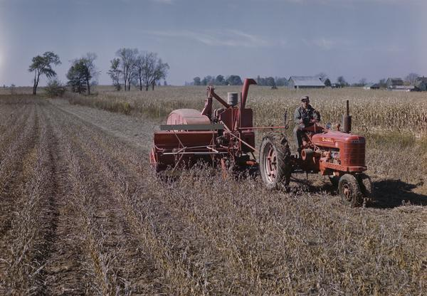 Farmer harvesting grain with a Farmall H tractor and harvester-thresher (combine).
