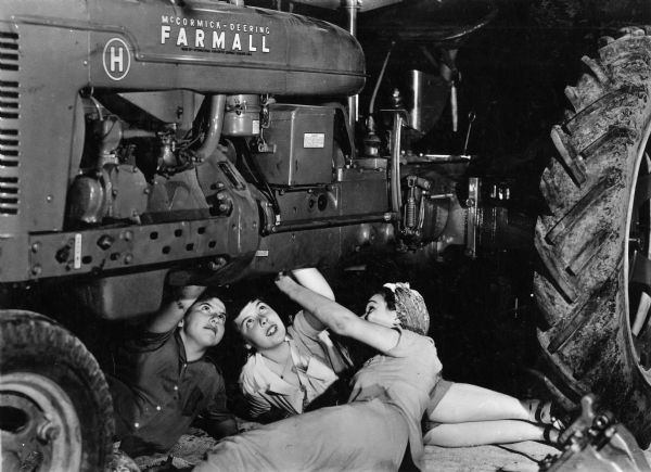 "Three women work under a Farmall H tractor. International Harvester's ""Tractorette"" program was intended to teach women to operate and maintain tractors while their husbands were serving in the military during World War II."