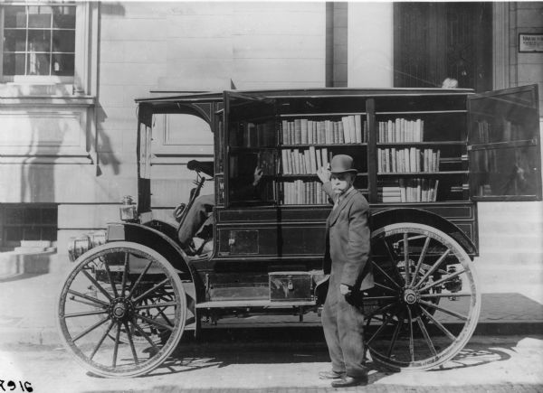 "An International Auto Wagon with a rear compartment containing shelves of books is parked outside a library.  A man in a bowler hat is selecting a book from what appears to be a ""bookmobile."""