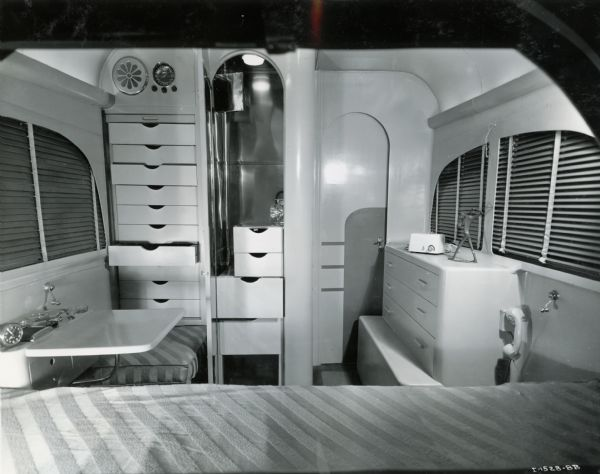 "The bedroom of an International ""Jungle Yacht"", equipped with a bed, telephone, dresser, extra clothing storage, and windows. The ""Jungle Yachts"" were specially produced by International Harvester for one of the Commander Attilio Gatti's expeditions to the African Congo."