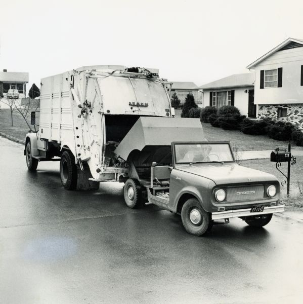 International Scout truck with dump box loading refuse into a garbage truck in a suburban neighborhood.