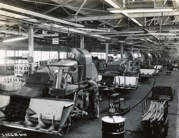 Men working on combines (harvester-threshers) on an assembly line at International Harvester's East Moline Works. The factory was constructed in 1933 and was located at 1100 3rd Street.