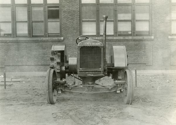 "Experimental McCormick-Deering 15-30 tractor parked outside a brick building (possibly International Harvester's Tractor Works in Chicago).  This photograph was taken by International Harvester's engineering department.  The original caption reads ""15-30 wide tread tractor with short turn steering device - front view."""
