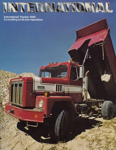 "Front cover of an advertising brochure for International Paystar 5000 construction trucks.  Features a color photograph of a Paystar 5000 dump truck in a quarry with the motto, ""it's building its own reputation."""