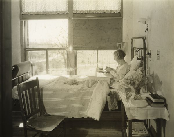 Tuberculosis patient sitting in a sanatorium bed making dolls.