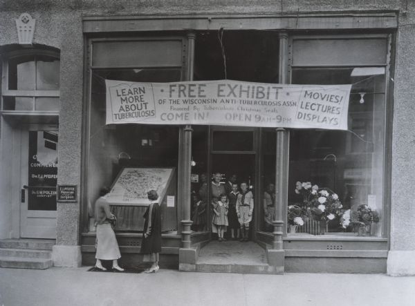 Wisconsin Anti-Tuberculosis Association exhibit advertised in the storefront of a building in New London, Wisconsin. Two women are looking through the window of the storefront, while another woman and several children stand in the doorway.