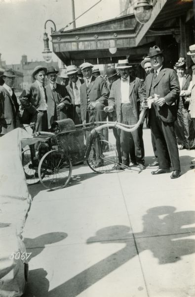 Men gathered outdoors around a cotton picking machine exhibited at the National Implement and Vehicle Association Meeting.