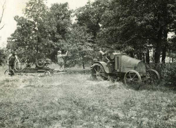 Two farmers operating a pesticide sprayer while another man looks on from atop a nearby International 8-16 tractor.
