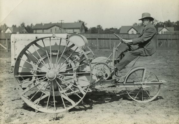 A man sitting behind the wheel of an experimental tractor.