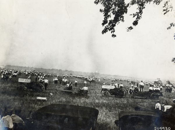 Large crowds gather over a farm field to view tractor demonstrations. Tractors include the International Harvester Mogul 8-16.