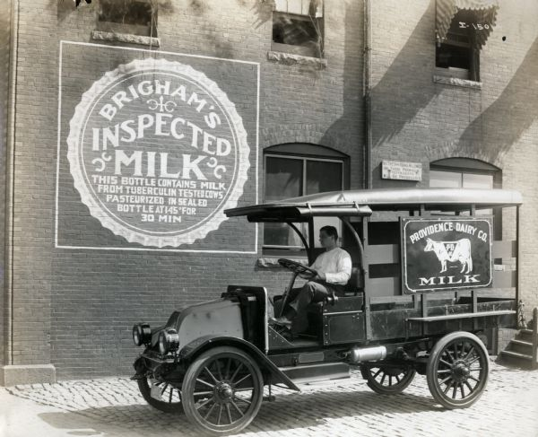 "A man sits at the wheel of an International Model F (or 31) truck operated by the Providence Dairy Company. The truck sits outside of a building with the sign ""Brigham's Inspected Milk."""