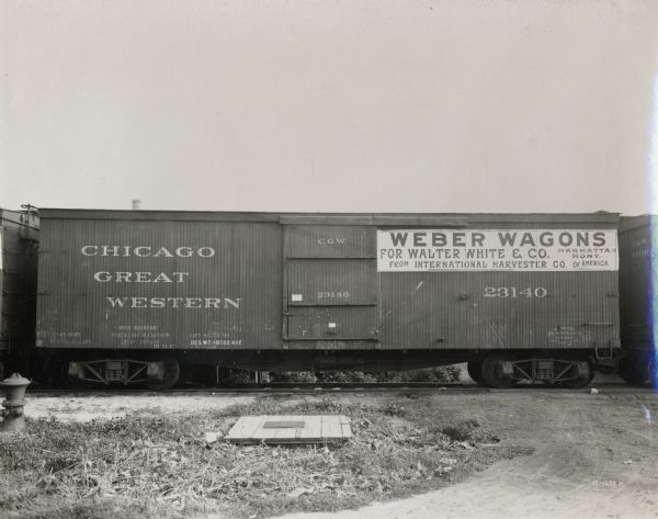 A boxcar in  a Chicago Great Western train carrying International Harvester Weber wagons. A sign on the car indicates that the wagons are bound for Walter White and Company in Manhattan, Montana.