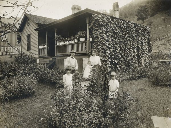 "A family of five poses in front of an International Harvester ""company house"" in the coal mining town of Benham."