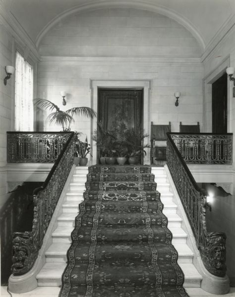 Front entrance hall at Cyrus McCormick, Jr.'s residence at 50 East Huron Street, with marble stairs and Cael stone walls. The view is from the ground floor to the first floor. The door at the top of the stairs leads to the Tapestry Room; the door on the right is to the Main Hall.