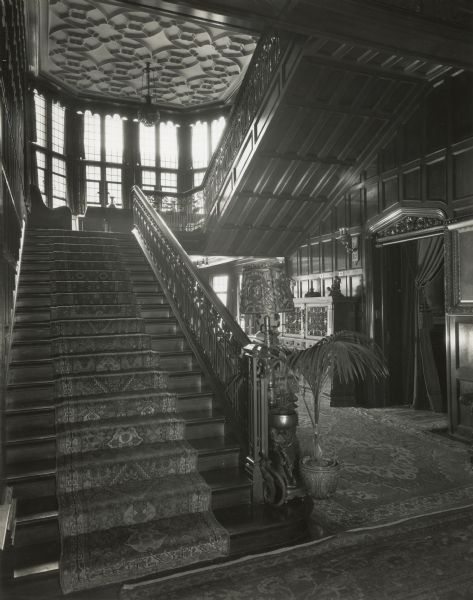 "Stairway from the main hall to the second floor at Cyrus McCormick,Jr.'s residence at 50 East Huron Street, with a view of the house's east windows. The door to the Empire Room is at right. Although they can barely be seen in the picture, writing on the back of the photograph identifies the painting at the extreme right of the photograph as that of Cyrus H. McCormick (the 1st), and the rug hanging on the wall at the top of the stairs at the far left of the photograph as a ""valuable Sepahan prayer rug."""