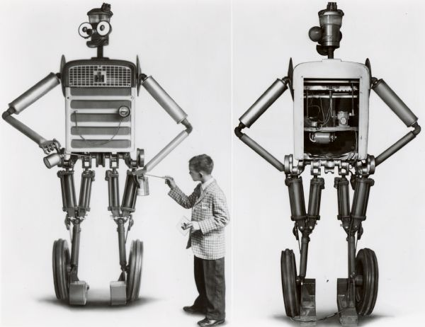 "Front and rear view of ""Tracto,"" a robot made of tractor parts for International Harvester's exhibits at state fairs. The front view features a young boy in tie and sports coat who appears to be touching Tracto's hand with a screwdriver, and holding a square object with the International Harvester logo in the other. Tracto poses with oil can and a can of IH tractor Hy-Tran fluid. From the original press release: ""the eight-foot 'talking' robot is assembled from 227 farm tractor and implement parts. Robot is equipped with two-way communication system and contains motor gear reducer for oscillating head and lifting right arm. Electrically powered, eyes light up through transformer installed in robot's stomach."" According to another press release, Tracto was voiced by ""district office personnel hidden from the view of passers-by, but advantageously located to spot interested viewers and provoke them into conversations."""