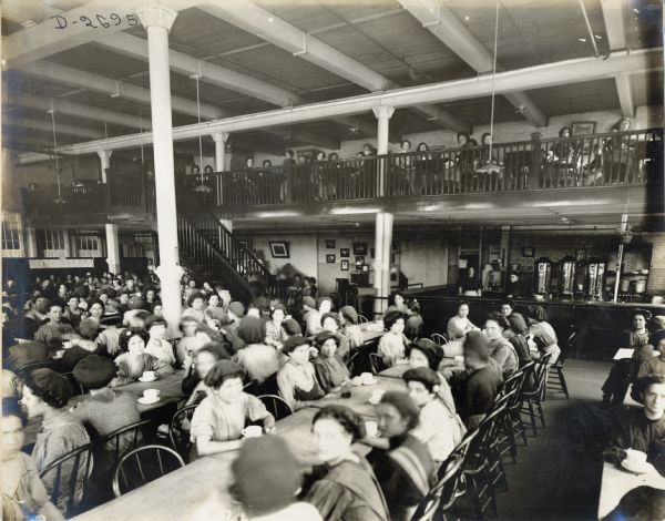 Female factory workers sitting at long tables with coffee cups at the Deering Twine Mill cafeteria. A large coffee bar is in the back right corner of the room.