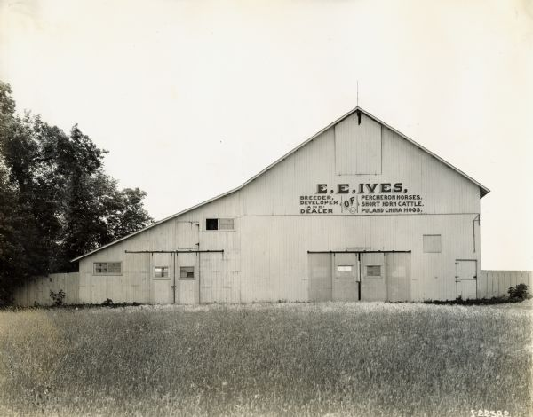 "Exterior view of a building on the E.E. Ives farm. A sign on the building reads, ""E.E. Ives, Breeder, Developer, and Dealer of Percheron Horses, Short Horn Cattle, Poland China Hogs."""
