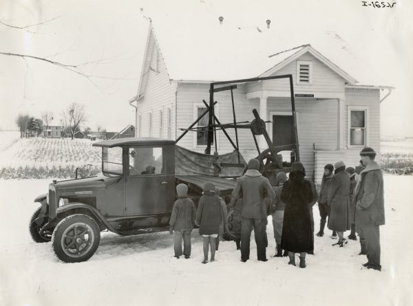 "A group of children and adults gathers around an International truck carrying a replica of McCormick's original reaper. The reaper replicas were made for the ""reaper centennial"" celebration, an International Harvester promotional event. The truck is parked in front of a rural schoolhouse."