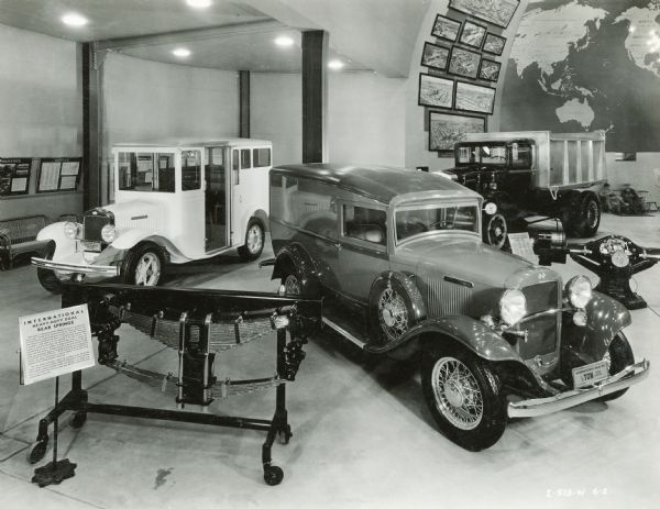 """International trucks on display in the International Harvester exhibit at the """"A Century of Progress"""" world's fair. Models include the International M-3 """"House to House Delivery"""" and the International D-1 """"1/2 Ton Rated Capacity,"""" along with heavy-duty dual rear springs and a double-reduction drive rear axle."""